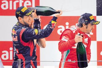Sebastian Vettel (left) celebrates his victory at the Indian Grand Prix; and Fernando Alonso came in second. Photo: Prakash Singh/AFP