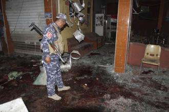 A file photo of a police officer inspects the site of a bomb attack at a coffee shop in Kirkuk, 250 km north of Baghdad. Photo: Reuters