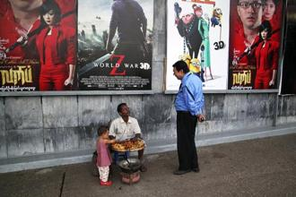 A file photo of a  man selling snacks under movie posters on the walls of a theatre in downtown Yangon. Photo: Jared Ferrie/Reuters