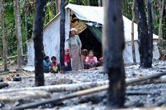 A file photo shows a Rohingya Muslim family sitting outside their temporary shelter at a village in Minpyar in Rakhine state. Photo: AFP