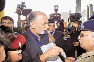 Tarun Tejpal shows his identity card to a security guard as he enters the New Delhi airport on Friday while on his way to Goa. Photo: AFP