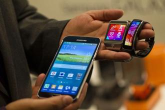 An employee displays a Galaxy S5 smartphone (left) and new Samsung Gear (center) and Gear Fit wristwatch devices during a Samsung Electronics conference at the Mobile World Congress in Barcelona, Spain, on 23 February 2014. Bloomberg