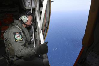 A military officer looks out of a transport plane during search for the missing Malaysia Airlines MH370 plane over South China Sea on Tuesday. Photo: Reuters