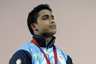 Vikas Thakur of India poses on the podium after winning the silver medal in the Men's 85kg weightlifting competition at the Clyde Auditorium during the 2014 Commonwealth Games in Glasgow, Scotland, on Monday. Photo: AFP