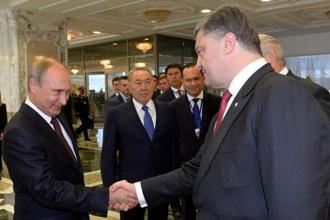 Russian President Vladimir Putin (left) and Ukrainian President Petro Poroshenko (right) shake hands during a summit in Belarus' capital of Minsk on Tuesday. Photo: AFP