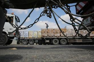A Palestinian man stands on a truck loaded with goods after it entered the Gaza Strip from Israel through the Kerem Shalom crossing on Thursday in Rafah in the southern Gaza. Photo: AFP