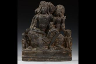 The holy family: Shiva in three-headed form is seated in lalitasana on his vahana Nandi, his left arm embracing his consort Parvati.  Flanking the recumbent Nandi are Ganesha and Kumara who stand in attendance.