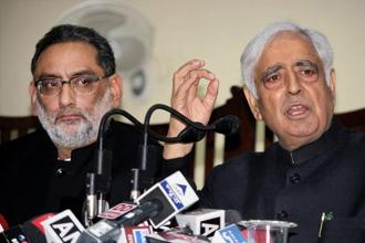 Jammu and Kashmir chief minister Mufti Mohammad Sayeed with minister Haseeb Drabu speaks with media during a press conference in Jammu on Sunday. Photo: AP