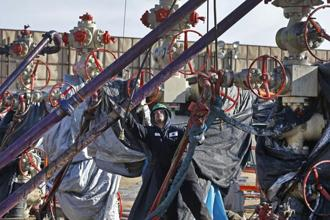 A worker adjusts pipes during a hydraulic fracturing operation at a gas and oil well pad near Mead, Colo. Photo: AP