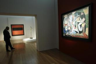 "A Christie's employee walks in a room next to Pablo Picasso's ""Les femmes d'Alger (Version ""O""), (R), during a media preview on May 1, 2014, at Christie's in New York.  Photo:AFP"