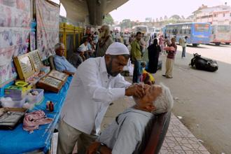 Traditional Indian dental worker Allah Baksh takes measurements for dentures from a customer at his roadside stall at K.R. Market bus stand in Bangalore. Photo: AFP