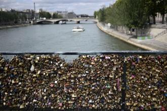 Paris' iconic Pont des Arts bridge has become a shrine for lovers, who seek to immortalise their love by leaving an initialled padlock attached to its metallic grid railings, and throwing the key in the Seine river flowing below. AP