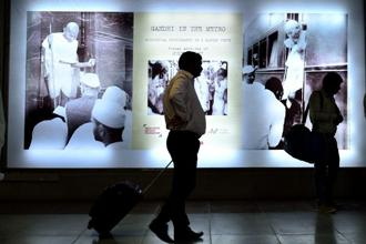 Commuters carry their bags past the main banner of the exhibition. Photos: Priyanka Parashar/ Mint