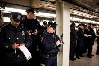 Police officers have their roll call in the Times Square subway stop following a series of terrorist attacks in Paris on November 14, 2015 in New York City. Security in New York City has increased following the coordinated assault on Paris which ISIS claimed responsibility for. Photo: AFP