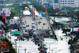 Commuters stuck on a submerged flyover. Photo: AFP
