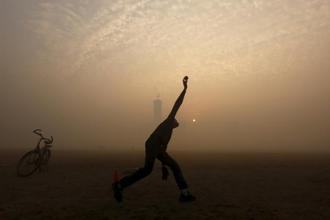 A boy bowls while playing cricket in a public park amidst heavy fog on a cold winter morning in Kolkata on 30 December. Photo: Reuters