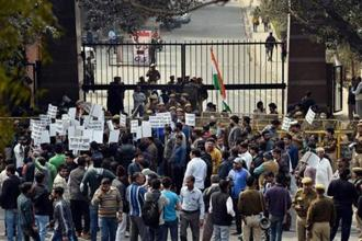 "Residents of Munirka village protest outside JNU's north gate  against the organising of a meet to ""mourn"" the hanging of 2001 Parliament attack convict Afzal Guru. Photo: PTI"