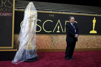 A security guard stands next to an Oscar statue covered in plastic on the red carpet at the entrance to the Dolby Theatre as preparations continue for the 88th Academy Awards. Photo: Reuters