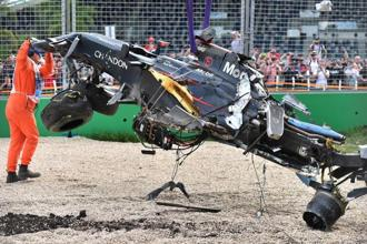 A track official assists the removal of McLaren driver Fernando Alonso's car following a crash during the Australian Formula One Grand Prix at Albert Park in Melbourne on Sunday. Photo: AP