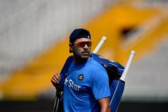 Yuvraj Singh walks with his equipment during a training session at the Punjab Cricket Association stadium in Mohali on 26 March, ahead of the World T20 match against Australia. Photo: AFP