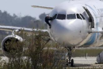 A man climbs out of the cockpit window of the hijacked Egyptair Airbus A320 at Larnaca Airport in Larnaca, Cyprus.  Photo: Reuters