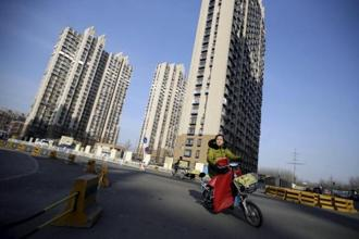 A file photo of a woman riding past a residential compound in Beijing. S&P said the China's reform agenda is on track but likely to proceed more slowly than expected. Photo: Reuters