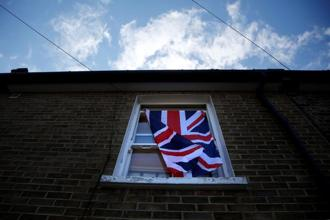 A British flag flutters in front of a window in London after the Brexit vote.
