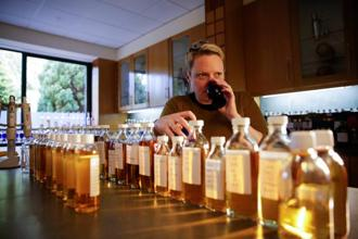 Emma Walker, a whisky specialist and blender at Diageo Plc, tests the aroma of a single malt, single grain whiskey taken from a sample bottle. Photo: : Matthew Lloyd/Bloomberg