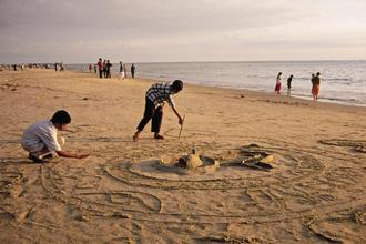 Children building a sandcastle on Kozhikode beach. Photo: Alamy