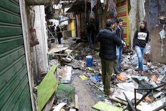 Iraqi security forces inspect the site of a bomb attack at a market in central Baghdad on Saturday. Photo: Reuters