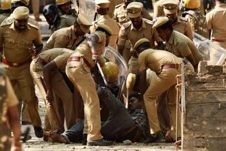 "Riot control police take away one of the pro-Jallikattu protesters during a clash at Marina Beach in Chennai on Monday. Chennai city police commissioner S. George said police tried to grab ""anti-social elements"" that had intruded into the protests. Photo: PTI"