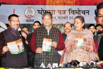 Uttarakhand chief minister Harish Rawat releases the party's poll manifesto in Dehradun on Sunday. Photo: PTI