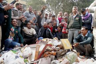 A file photo. MCD workers shout slogans while piling up garbage near deputy chief minister Manish Siosodia's office during a protest over their demands in east Delhi. Photo: PTI