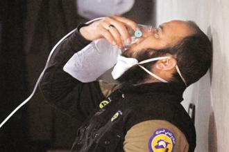 A civil defence member breathes through an oxygen mask, after what rescue workers described as a suspected gas attack in the town of Khan Sheikhoun in rebel-held Idlib, Syria. Photo: Reuters