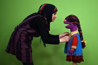 An April 2016 photo shows Raziya Nazari preparing Zari, the muppet, for a recording at an Afghan television studio in Kabul. Photo: Wakil Kohsar/AFP
