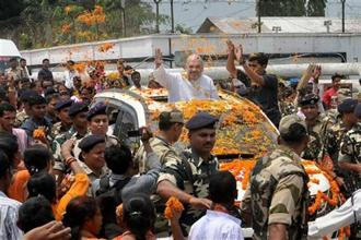 BJP president Amit Shah waves at supporters on being welcomed at the Agartala airport in Tripura on Saturday. Photo: PTI