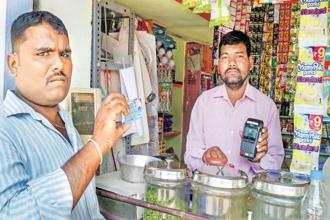 Anjaneyulu (left), a farmer, uses his Rupay debit card to pay for purchases at a store owned by Ramaswamy, at Ibrahimpur. Photo: Yunus Y. Lasania/Mint