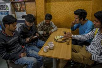 A file photo. Kashmiri students browse internet on their mobile phones as they sit inside a restaurant in Srinagar. Photo: AP
