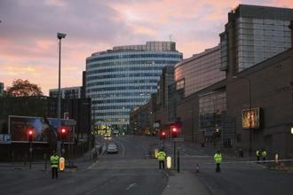 Police stand guard at the scene of a suspected terrorist attack after a pop concert by American singer Ariana Grande in Manchester on Tuesday. At least 22 people were killed and 59 wounded in the blast. AP