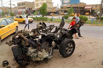 File photo: Civilians pass a wreckage of the car bomb explosion in Baghdad on 20 May 2017. Photo: AP