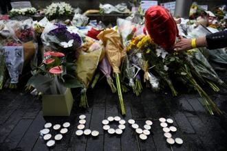 A person lays a floral tribute at the vigil at Potters Field Park, two days after three men wrought destruction in London, killing seven people and injuring 48 on Monday. Reuters.