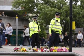 Police officers walk by floral tributes in the London Bridge area of London on Monday. Photo: AP