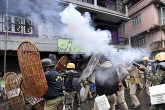 Security personnel fire teargas shells during a protest by GJM activists in Darjeeling on Saturday. Photo: PTI