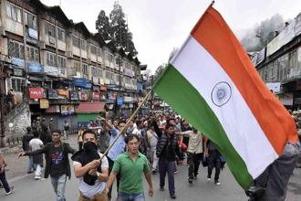 Gorkha Janmukti Morcha (GJM) supporters wave a tricolour during a protest rally in Darjeeling on Sunday. Photo: PTI