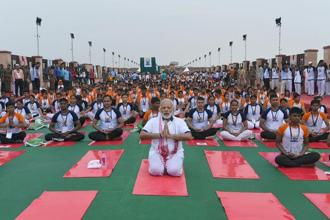 Rains failed to dampen the spirits of about 50,000 people who joined an outdoor yoga session with the prime minister in a park in Lucknow. Photo: AFP