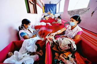 Staffers sorting out donated clothes at the Delhi-based NGO Goonj. Photo: Priyanka Parashar/Mint
