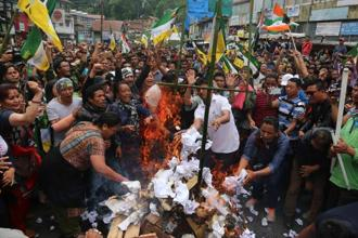 Gorkha Janmukti Morcha (GJM) supporters burn copies of the Gorkhaland Territorial Administration (GTA) agreement during a protest in Dagapur village on the outskirts of Siliguri on Tuesday. Photo: Saibal Das/Mint