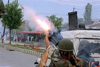 CRPF personnel fire teargas shells to disperse the protesters during a clash which erupted after Eid prayers in Srinagar on Monday. Photo: PTI