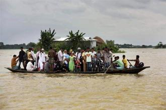 Villagers shift to safer places using a boat at Morigaon district in Assam on Tuesday. PTI