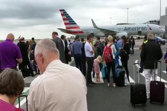 Passengers stand on the tarmac after being evacuated at Manchester Airport, England, Wednesday on 5 July. Photo: AP